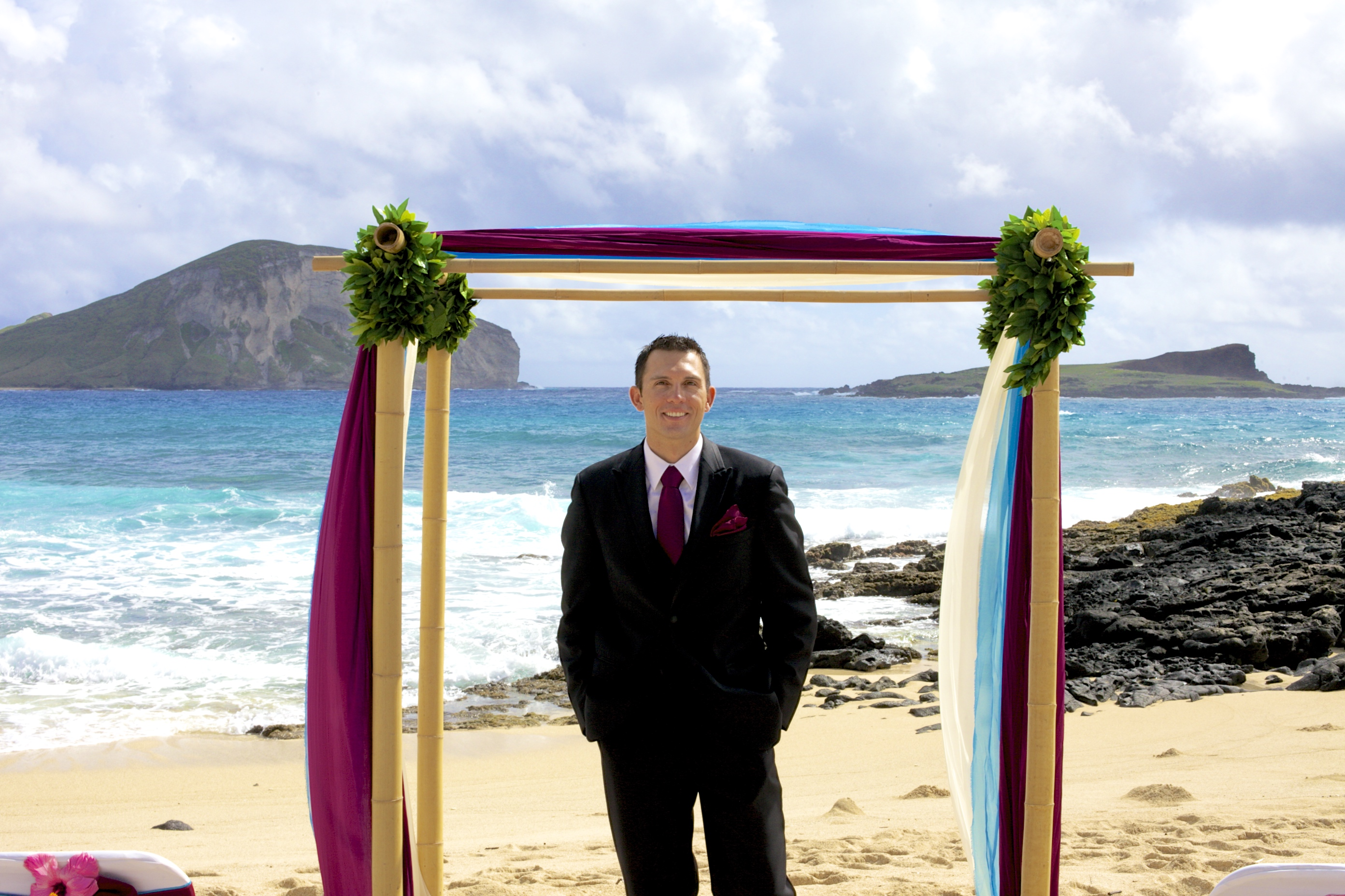 groom standing under the bamboo arch in Hawaii at his beach wedding